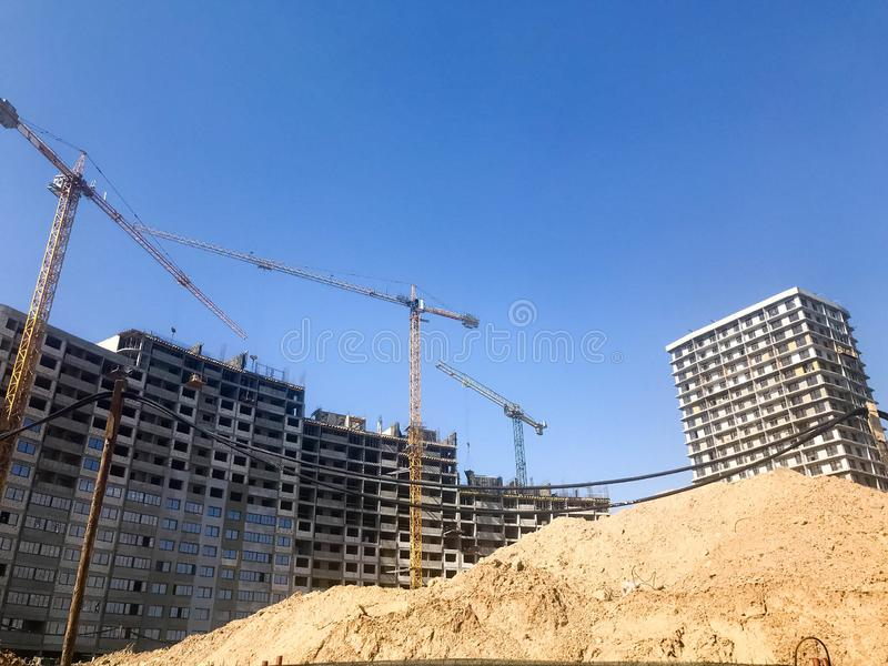 Building with the help of construction cranes of high reinforced concrete, panel, cast-frame, frame-block houses, buildings stock photo