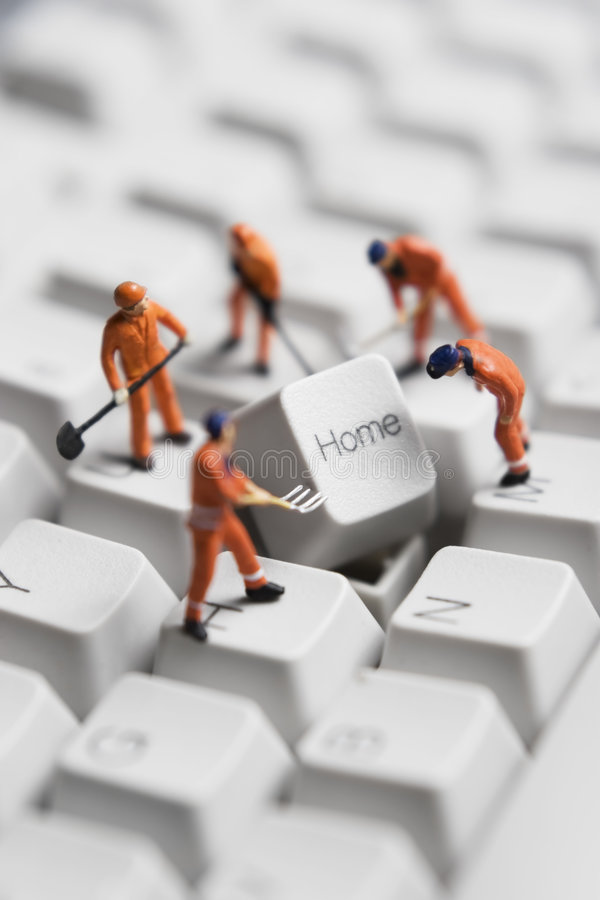 Building a home based business. Worker figurines posed around the Home key on a computer keyboard royalty free stock image