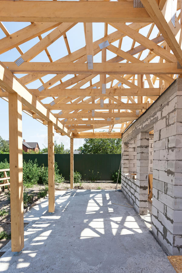 Building house from aerated concrete building blocks. New residential wooden construction home framing against a blue sky. royalty free stock photo