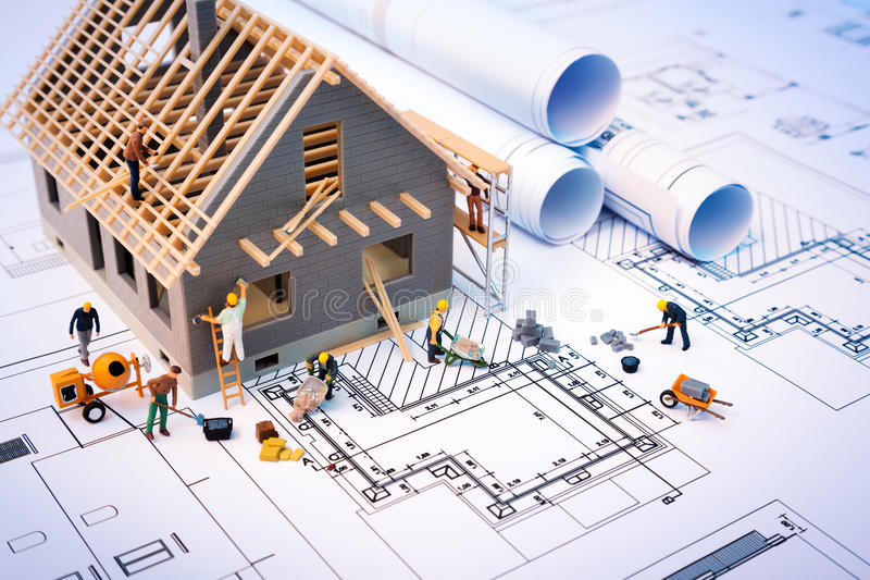 Building house on blueprints with worker. Construction project royalty free stock image