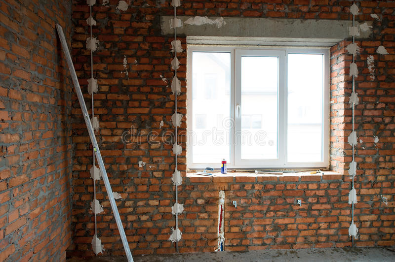 building house. Performed work on electrical wiring and installation of windows, prepared the surface of brick walls to gypsum pl stock images