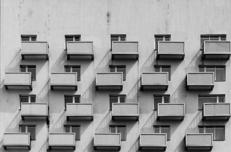 A building with identical balconies and windows with a shadow on stock images