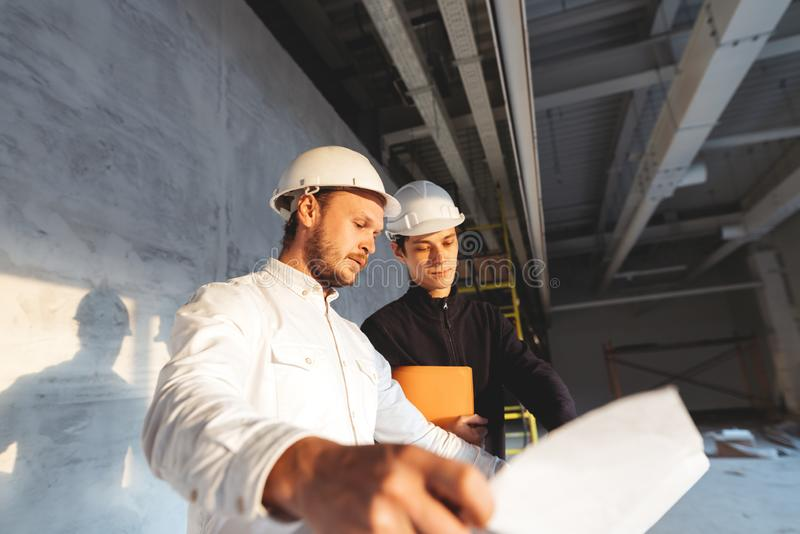 Building industry. Young engineer discussing with building worker on construction site stock photography