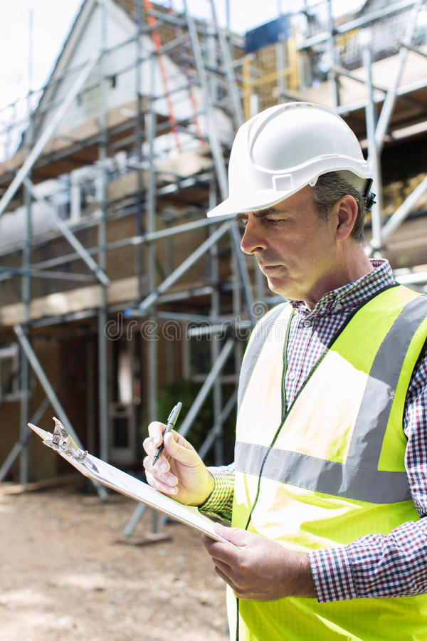 Building Inspector Looking At House Renovation Project. Building Inspector Looks At House Renovation Project stock photography