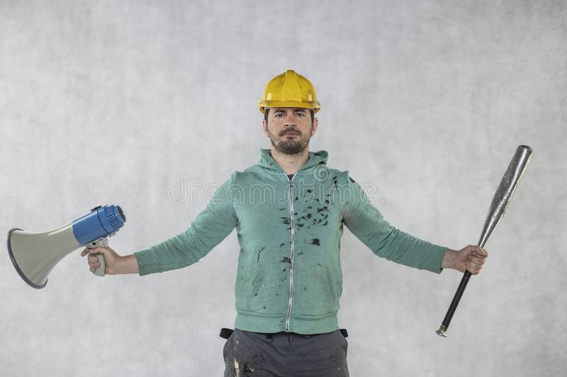 The building investor is holding a megaphone and a baseball bat in his hands stock photo