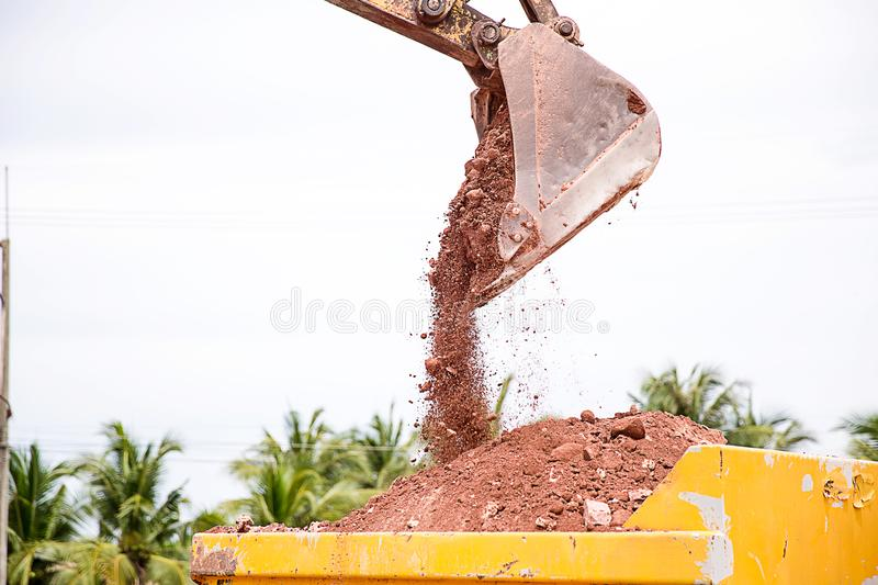 Building Machines: Digger loading trucks with soil. Excavator loading sand into a dump truck. Work in the quarry. Excavator Loading Dumper Truck at royalty free stock photography