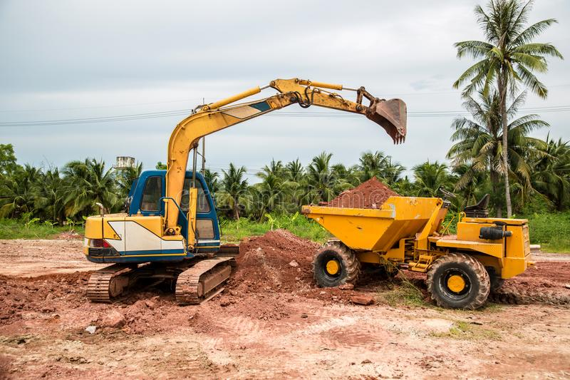 Building Machines: Digger loading trucks with soil. Excavator loading sand into a dump truck. Work in the quarry. Excavator Loading Dumper Truck at stock images