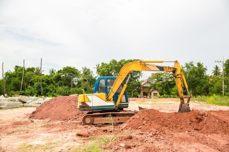 Building Machines: Digger loading trucks with soil. Excavator loading sand into a dump truck. Work in the quarry. Excavator Loading Dumper Truck at stock image