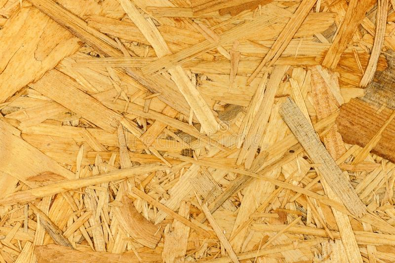 Building material. OSB boards are made of brown wood chips sanded into a wooden background. Background from wood fiber board.  stock photo