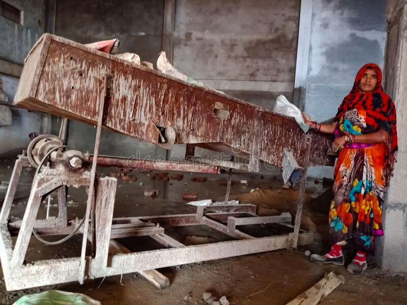 building materials mixing machine kept at construction site presenting by village woman in India January 2020 stock photography