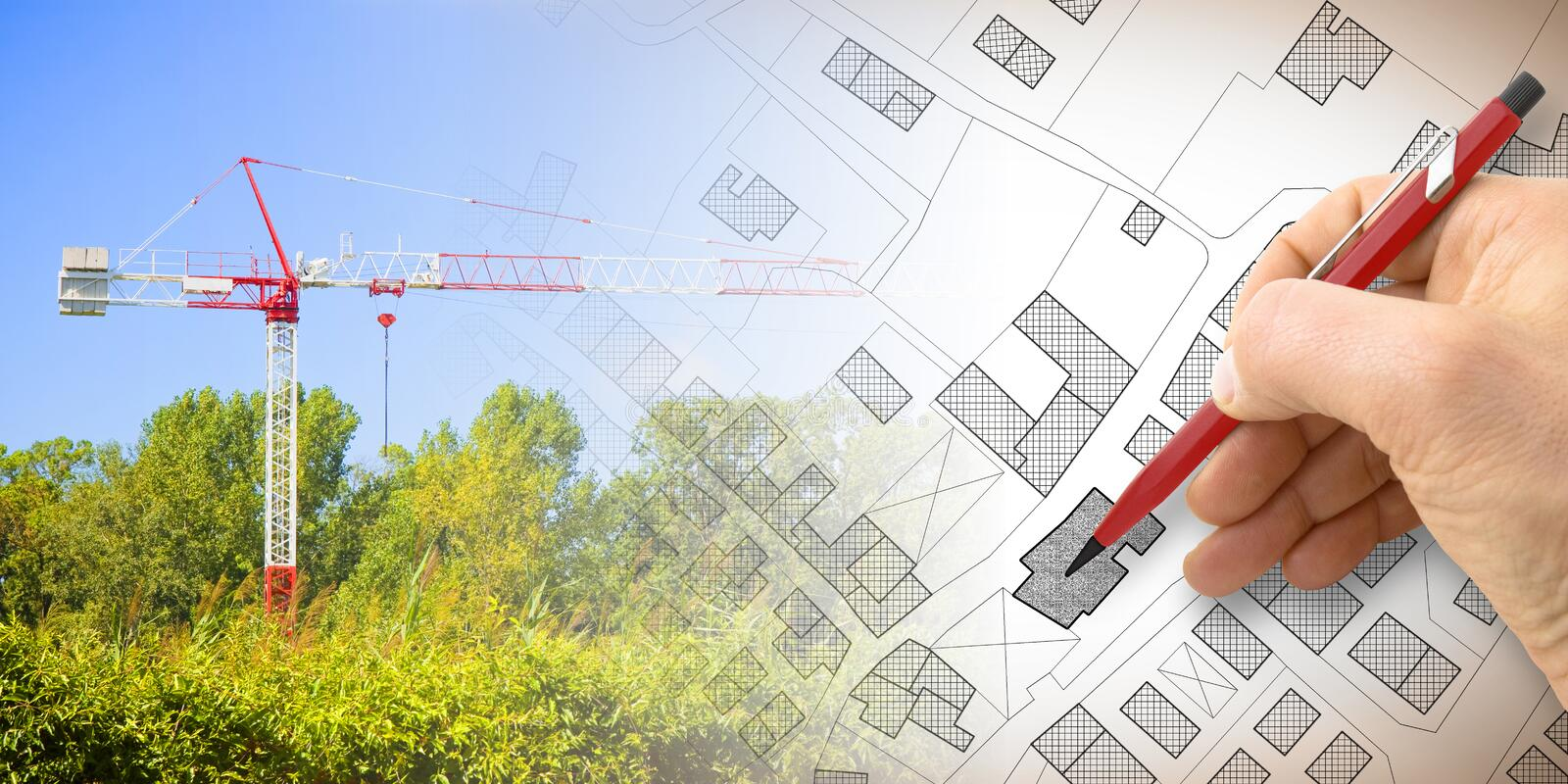 Building a new city - concept image with and drawing an imaginary cadastral map of territory with buildings, fields and roads and. A tower crane in a royalty free stock images