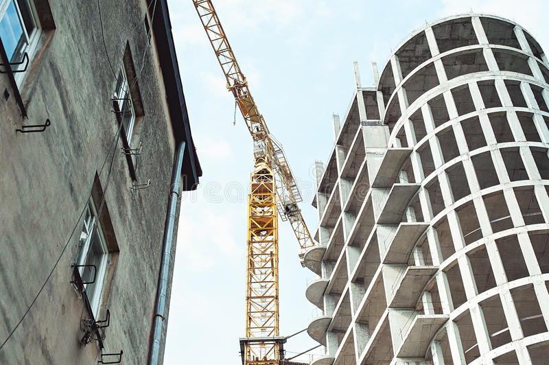 Building a new home with the help of tower cranes. old building from left side royalty free stock photography
