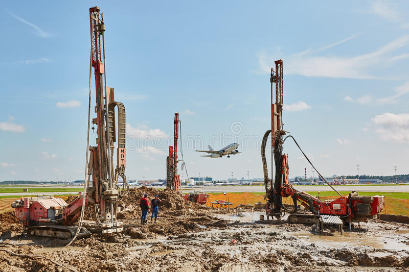 Building om runaway. Some types on drill machines on runaway in airport stock image