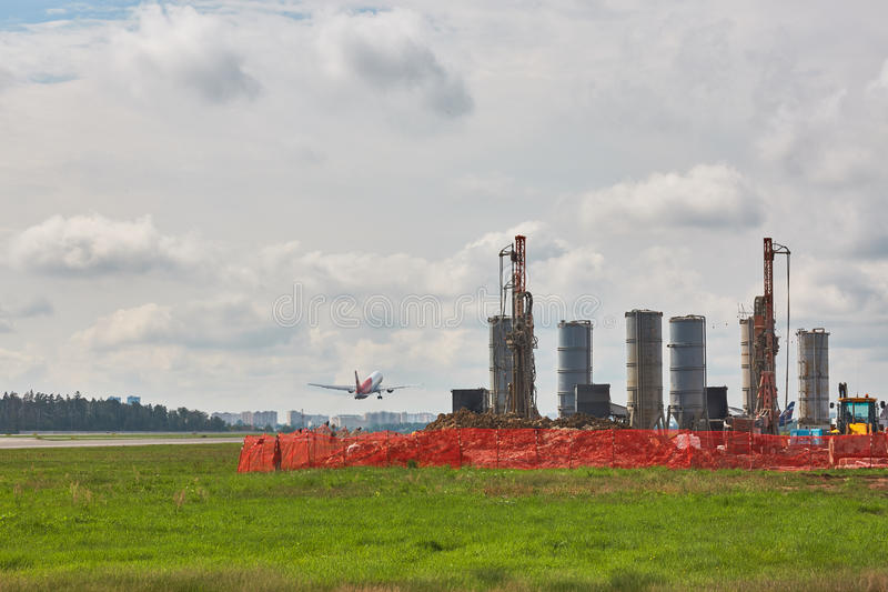 Building om runaway. Some types on drill machines on runaway in airport stock images