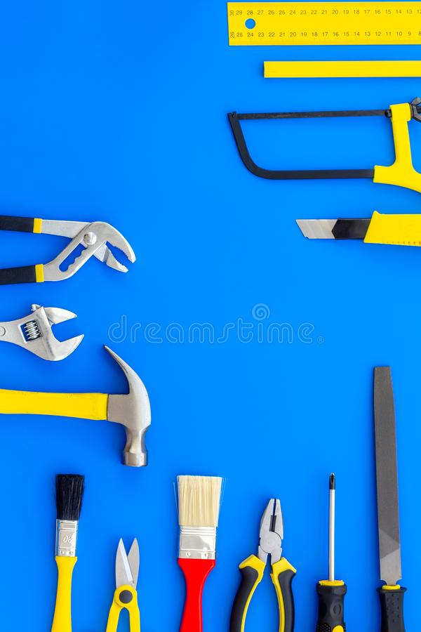 Building, painting and repair tools for house constructor work place set blue background top view space for text. Building, painting and repair tools for house royalty free stock images