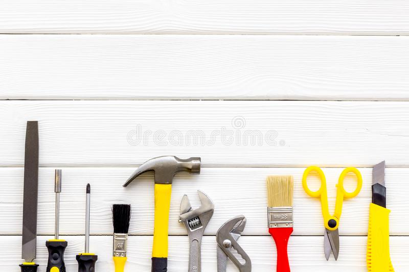 Building, painting and repair tools for house constructor work place set wooden white background top view space for text. Building, painting and repair tools for royalty free stock images