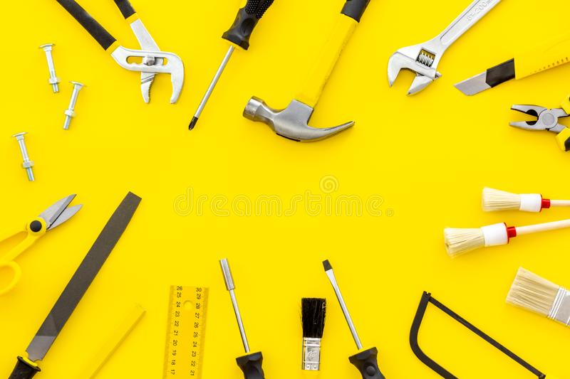 Building, painting and repair tools for house constructor work place set yellow background top view space for text. Building, painting and repair tools for house stock photography