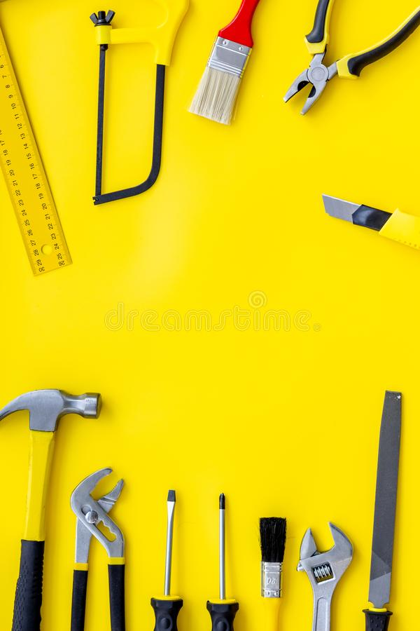 Building, painting and repair tools for house constructor work place set yellow background top view space for text. Building, painting and repair tools for house royalty free stock photo