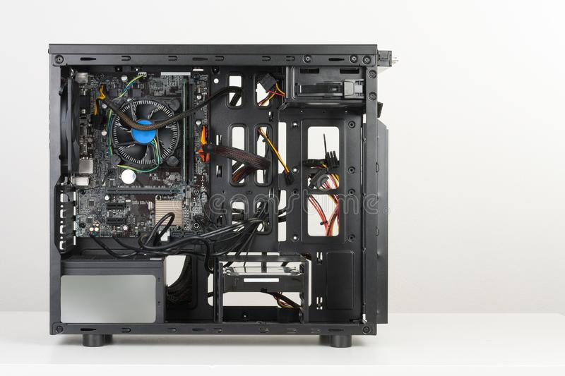 Building of PC, ATX motherboard inserted to black computer midi royalty free stock photography