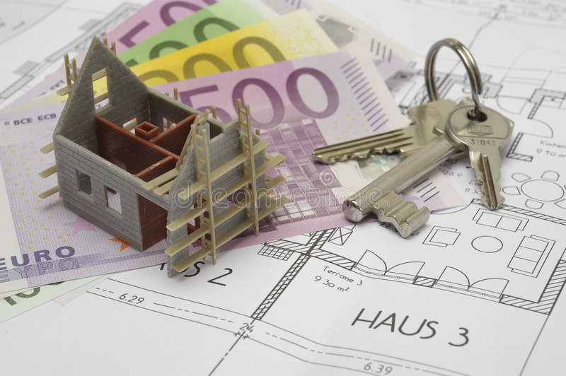 Building plan with keys and money. An architectonic or construction plan for building a house, symbolic with money and key stock photo