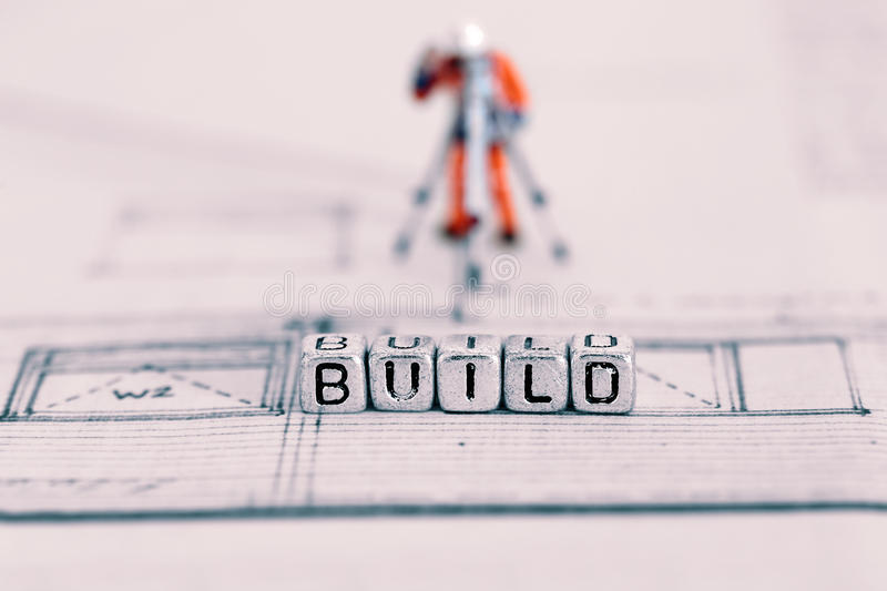 Building plan with the word build on beads and a model worker stock photos