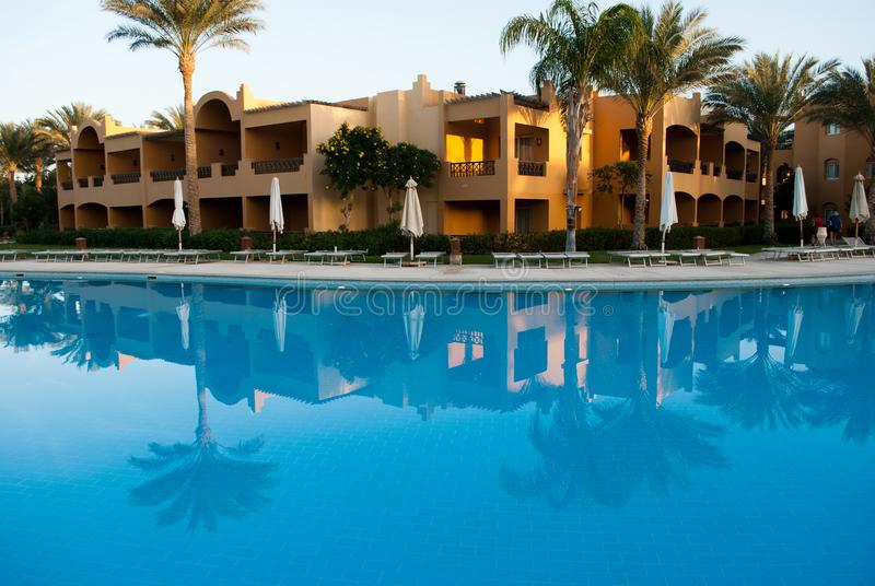 Building reflection on swimming pool water. Evening sun on building with two palms reflect to water mirror. Building reflection on swimming pool calm water royalty free stock image