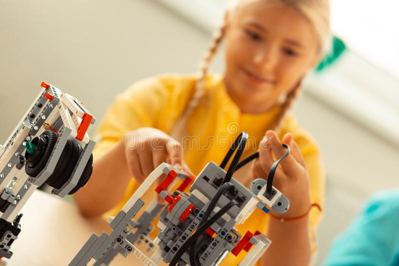 Girl figuring out how to fix her science project. Building a robot. Smiling girl pushing different parts of robot made of construction set figuring out how to royalty free stock images