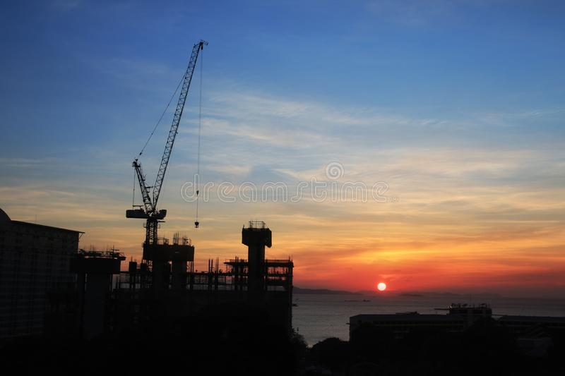 Building silhouettes and Industrial construction cranes on beautiful sunset stock photography