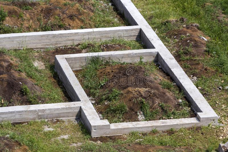 Building site in green field. Close-up detail of trenches dug in ground and filled with cement as foundation for future house. Bui royalty free stock image