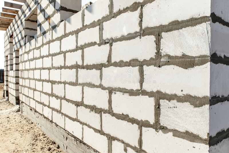 Building site of a house under construction. corner unfinished house walls made from white aerated autoclaved concrete blocks.  stock photography