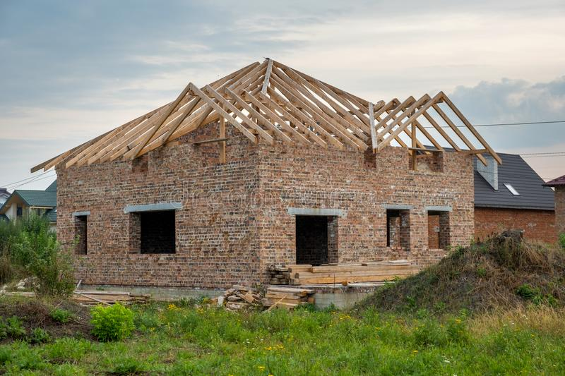 Building site with unfinished brick house with wooden roofing frame for future roof under construction stock images