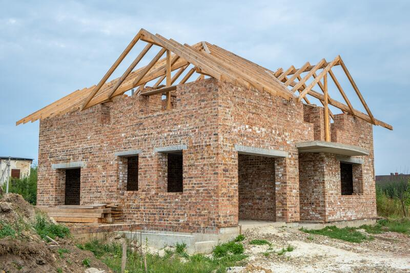 Building site with unfinished brick house with wooden roofing frame for future roof under construction stock photos