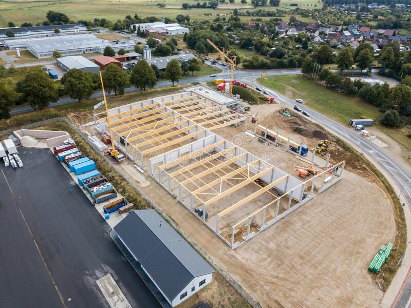 A building site wooden trusses are built on the concrete columns of a factory building. On a building site wooden trusses are built on the concrete columns of a royalty free stock photo