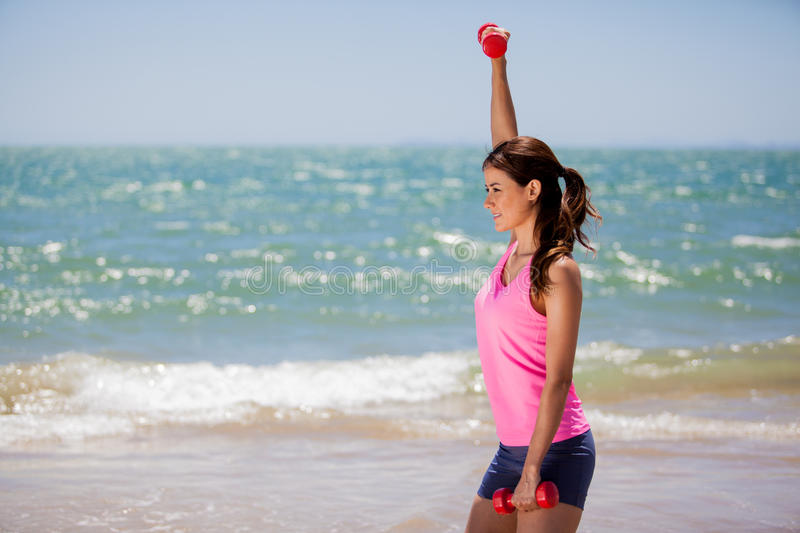 Building some muscle at the beach. Cute young brunette exercising and lifting weights at the beach stock photography