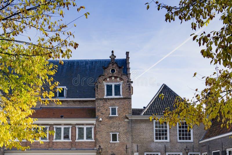 Building on square called Het Hof, Dordrecht, The Netherlands. Detail of monumental building on square called Het Hof, Dordrecht, The Netherlands. Tree leaves stock image