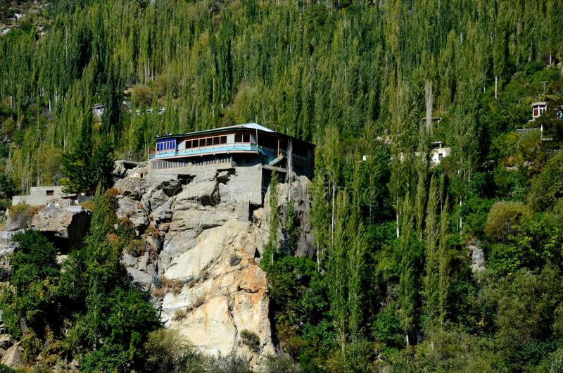A building stands on top of a rocky ledge in Hunza Valley Pakistan. Hunza, Pakistan - September 28, 2016: A primarily wood building stands on a rocky ledge stock photo