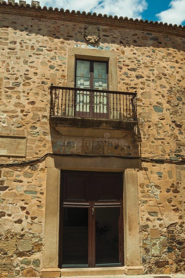 Building stone facade with door entrance and balcony at Caceres stock photos