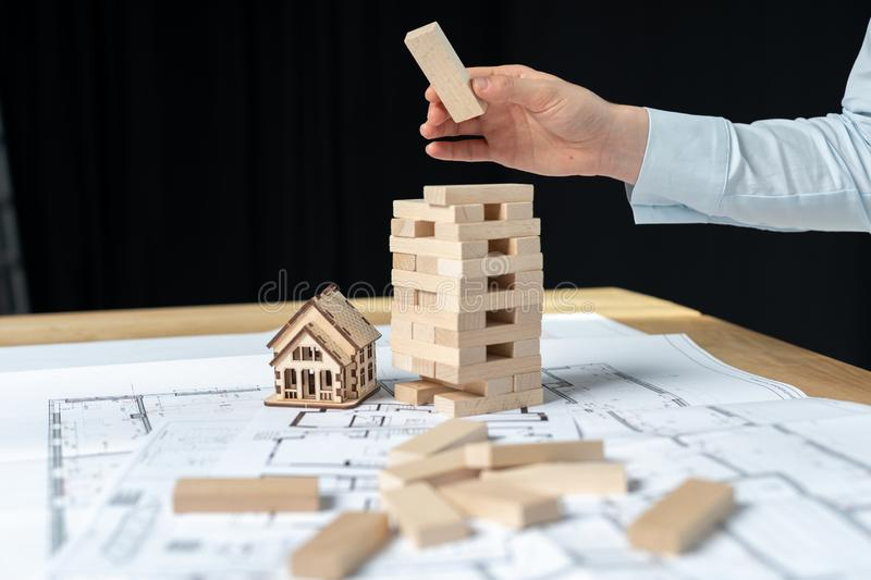 Building strategy concept. Confident architect lady in her formalwear standing indoor workroom. She holding jenga blocks in hand royalty free stock photography
