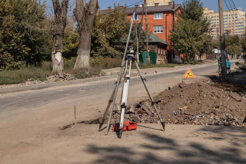 Building surveying equipment theodolite level tool during the repair of the roadway. Tula region, Russia. Building surveying equipment theodolite level tool royalty free stock image