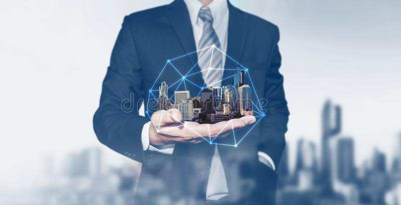 Building technology and business real estate investment. Businessman holding buildings on hand. Building technology and business real estate investment royalty free stock photo
