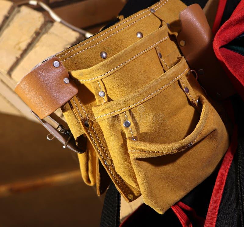 Building tool bag belt. Yellow tool bag. Leather bag.  royalty free stock photo