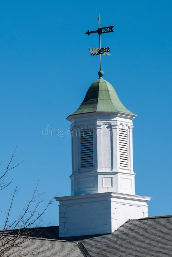 Building topping white cupola with green tin roof against a deep blue sky. stock photos