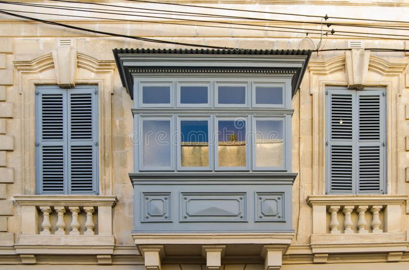 Building with traditional maltese balcony in historical part of Mosta. Window on the facade of a house in Malta royalty free stock photo