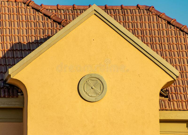Building with a triangular yellow facade below the brown roof. A building with a triangular yellow facade below the brown roof stock photography