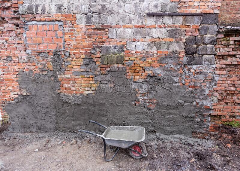 Building trolley with concrete in construction site and brick wall with concrete places . Concept of using of stock photo