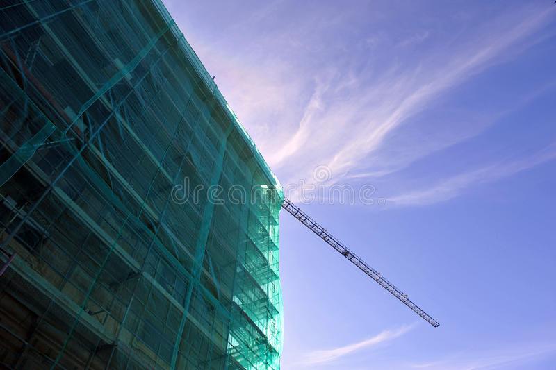 Building under construction, scaffolding, cranes. Tarpaulins and green nets protecting the scaffolding on the facade of a building under construction royalty free stock photo