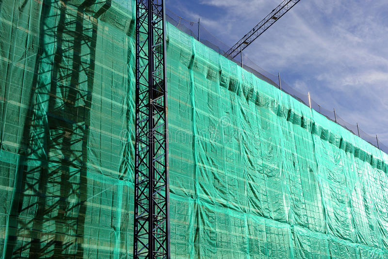 Building under construction, scaffolding, cranes. Tarpaulins and green nets protecting the scaffolding on the facade of a building under construction royalty free stock image