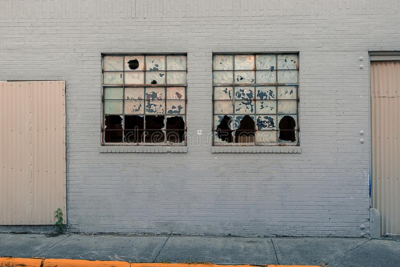 Building wall with broken windows in the city with shuttered dors stock photography