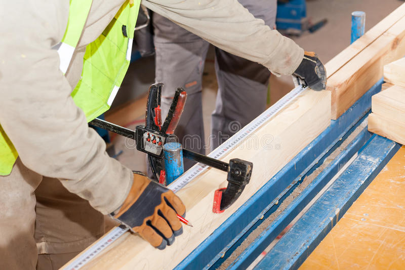 Building a wall for frame house. Worker make marks for cutting timber. Building a wall for frame house. Worker make marks for cutting timber stock image