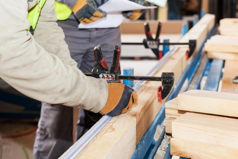 Building a wall for frame house. Worker make marks for cutting timber. Building a wall for frame house. Worker make marks for cutting timber royalty free stock photos
